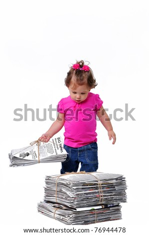 Toddler holding a stack of paper ready for recycling, teaching them to care about the environment when they are at an early age. - stock photo