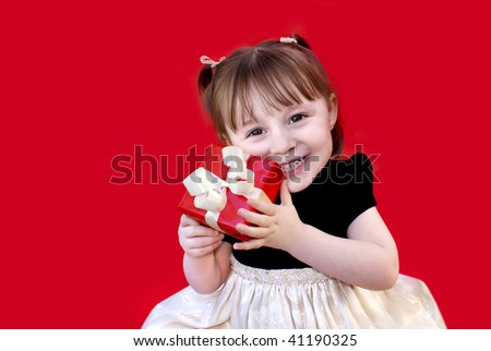 Toddler holds a red gift. - stock photo