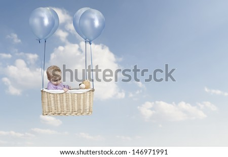 Toddler in a hot air balloon, flying in the air - stock photo