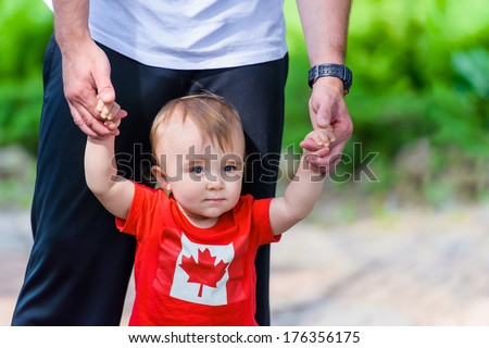 Toddler in Canada Flag shirt walking assisted by his father. Room for copy space.  - stock photo