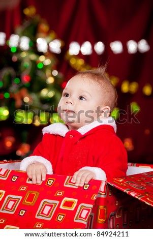 Toddler in Christmas red and white costume looking up - stock photo