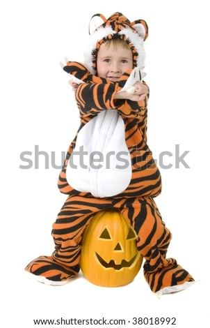 Toddler in halloween tiger costume sits on pumpkin