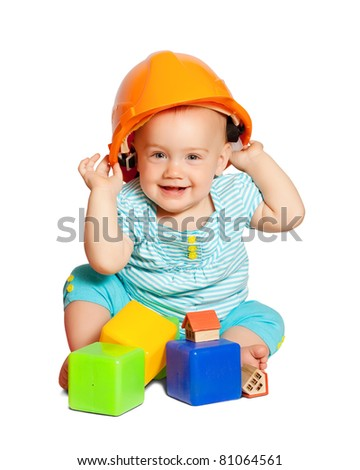Toddler in hardhat plays  with toy blocks over white background