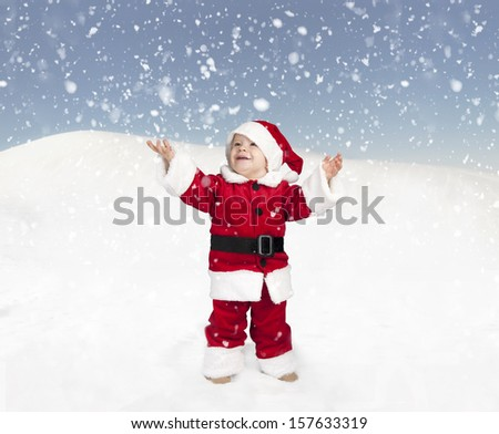 toddler in santa claus outfit standing in the snow and looking up - stock photo