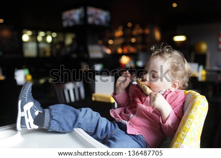 Toddler is eating kebab in a high chair at a restaurant - stock photo