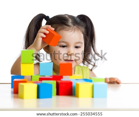 toddler kid girl builds a tower with colorful blocks - stock photo