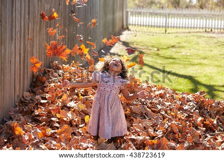 Toddler kid girl playing with autumn leaves latin ethnicity - stock photo