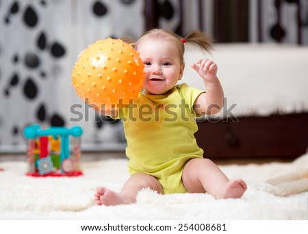 toddler kid playing with ball indoors at home - stock photo