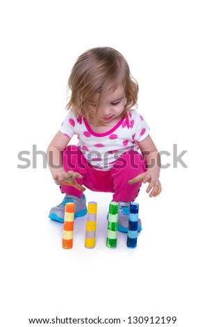 Toddler learning motor skills by paying attention to colorful crayons. Isolated on white with copy space.