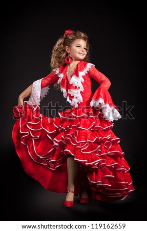 toddler little girl dancing flamenco in traditional spanish red dress. Adorable child from Andalusia with curly hair dancing Gypsy dance. Portrait of artist baby in carnival bellydancing costume - stock photo