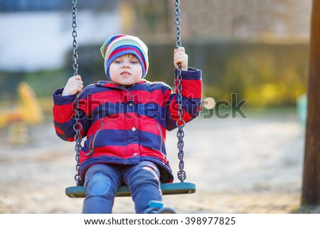 toddler little kid boy having fun with chain swing on outdoor playground. child swinging on warm sunny spring or autumn day. Active leisure with kids. Boy wearing colorful clothes - stock photo