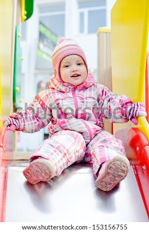 toddler on the slide in winter - stock photo
