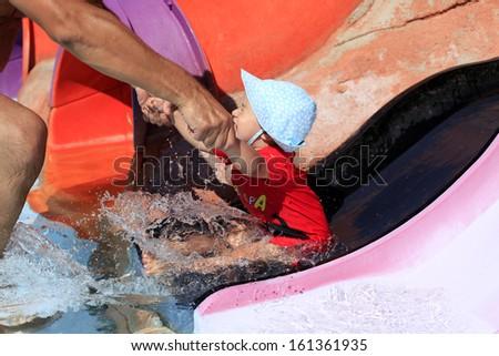 Toddler on water slide - stock photo