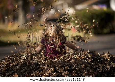 Toddler playing in leaves - stock photo
