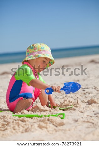Toddler playing in the sand on the beach - stock photo
