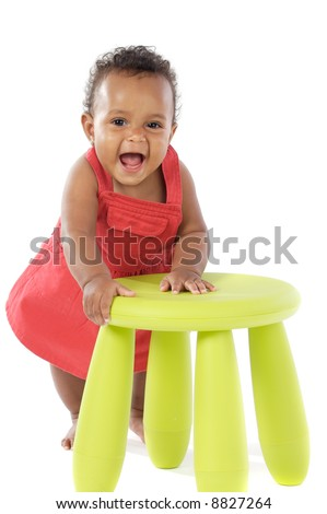 Toddler playing with a chair a over white background - stock photo