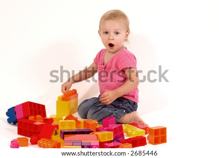 toddler playing with blocks, surprised - stock photo