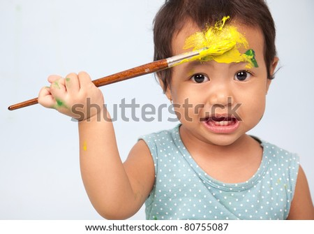 Toddler playing with brush and paint - stock photo