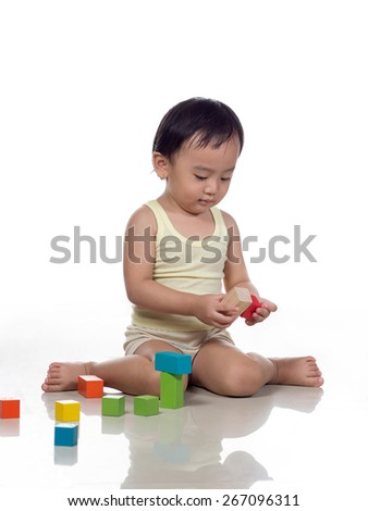 Toddler playing with colorfull building blocks - stock photo