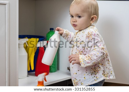 Toddler playing with household cleaners at home - stock photo