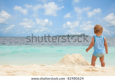 Toddler playing with sand on the tropical white beach - stock photo