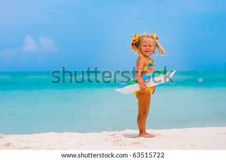Toddler pretty girl dressed in bikini standing on tropical beach with inflatable circle - stock photo
