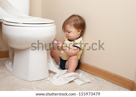 Toddler ripping up toilet paper in bathroom - stock photo