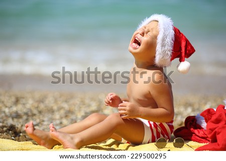 toddler Santa Claus on beach - stock photo