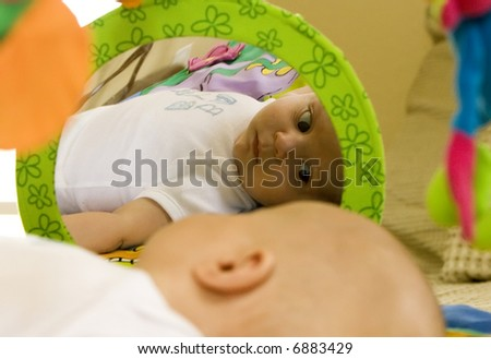 Toddler sees his reflecting in play gym - stock photo