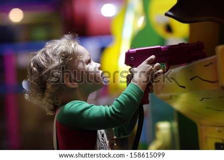 Toddler shooting a pistol at indoor playground - stock photo