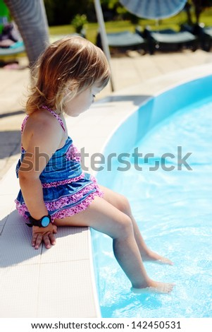 toddler sitting by the pool with legs in water