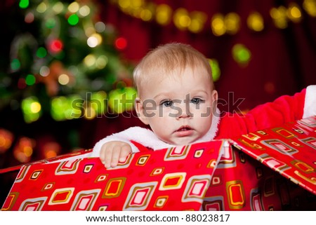 Toddler sitting in a large Christmas present box - stock photo