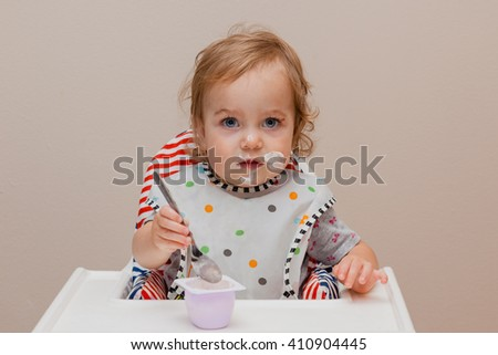 Toddler sitting in highchair and eating greek yogurt. Baby learning to eat and has yogurt on face. - stock photo