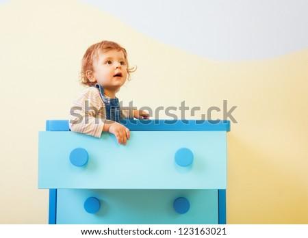 Toddler sitting in the box in kids room - stock photo