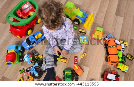 Toddler sitting on the floor surrounded by car toys