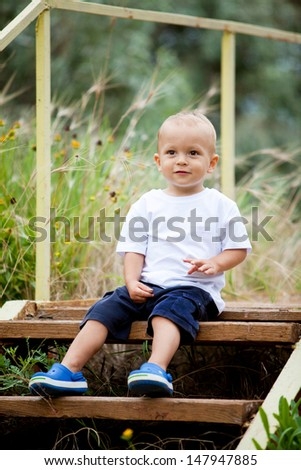 Toddler sitting upstairs in the garden/Toddler boy - stock photo