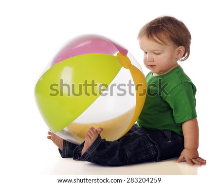 Toddler sitting with a big beach ball in his lap. - stock photo