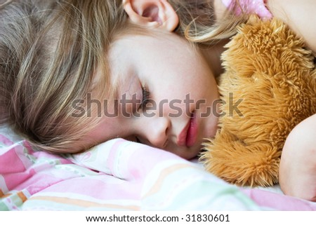 Toddler sleeping with her teddy bear - stock photo