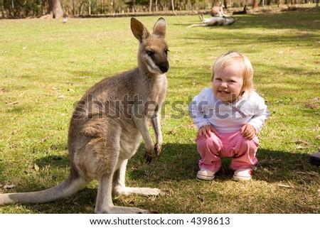 toddler smile next to small kangaroo - stock photo
