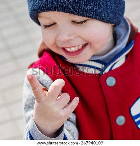 Toddler smiling child looking at a ladybug on her hand - stock photo