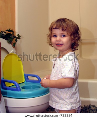 Toddler smiling next to her potty seat - stock photo