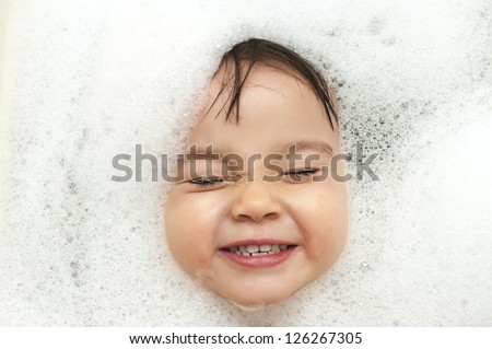 Toddler smiling showing face just above water surface.
