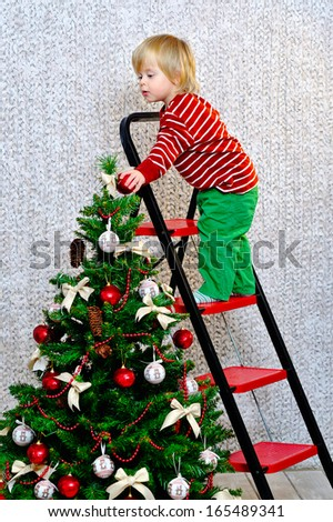 Toddler standing on the ladder and decorating Christmas tree - stock photo