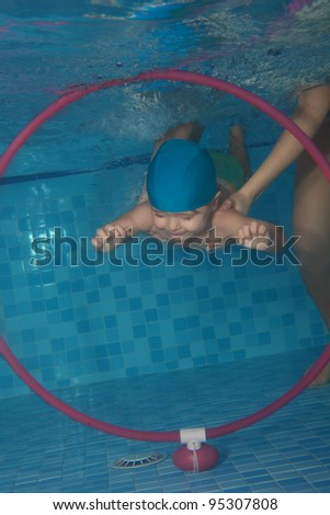 Toddler swimming exercises in swimming pool - diving in the hoop - stock photo