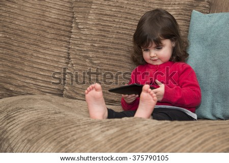 Toddler uses tablet PC - stock photo