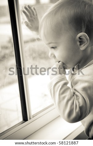 toddler waiting by the window, looking out - stock photo