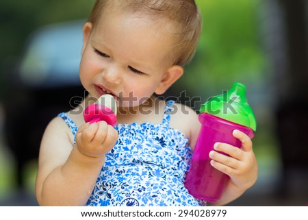 Toddler with homemade frozen treat and juice - stock photo