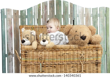 toddler with teddy bears standing in a straw trunk - stock photo