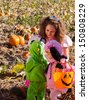 Toddlers and their mother dressed up in cute costumes at the pumpkin patch. - stock photo
