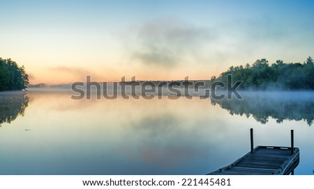 Toddy Pond, Maine, in the early morning light with reflected mist above the water and a small boat dock in the foreground. - stock photo